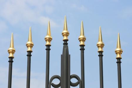 rejas de hierro: Picos de hierro forjado de una puerta, con un fondo de cielo azul