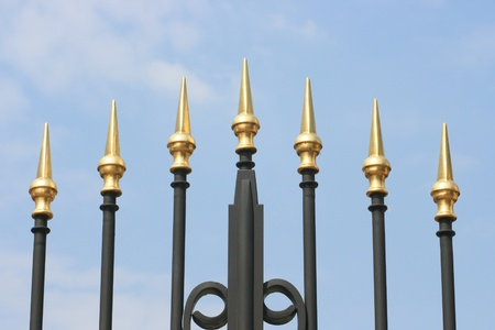 iron bars: Wrought iron spikes of a gate, with a blue sky background  Stock Photo