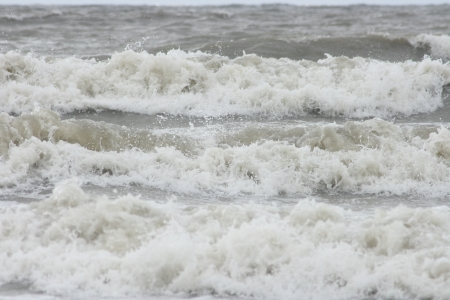 Waves with white crests inundate the sandy beach