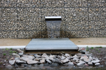 A stone wall built with gabions, from which water flows from