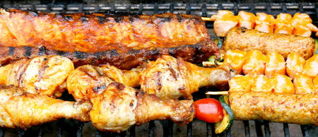 Various pieces of grilled meat on a grill grate photo