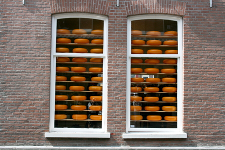 cheeses: Two windows with cheeses for sale
