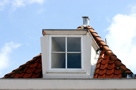 roof windows: A skylight on red tiled roof, blue sky in the background