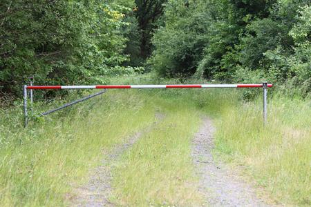 schlagbaum: Ein Turnpike blockiert den Weg in einer natürlichen Umgebung