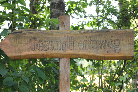 Brown wooden sign with the words: health-away