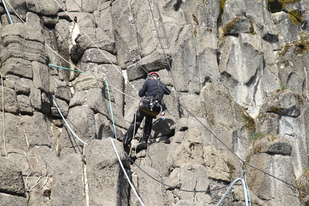 hedged: Kassel, Germany April 9, 2015: A rope access works in a rock wall Editorial
