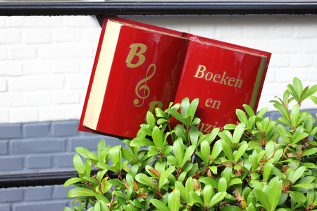 A red book of white pages, in the garden