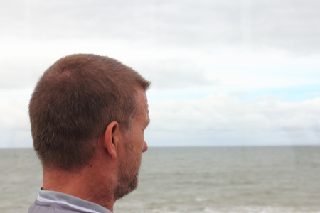 a man with short hair can look across the sea