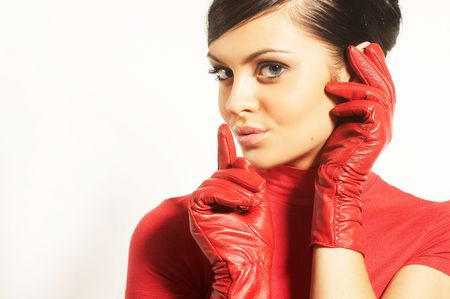 Atractive brunet in red blouse and red gloves near face photo