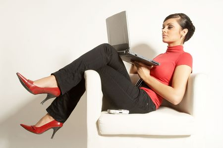 Atractive brunet businesswoman sitting with Laptop and phone on the white chair Stock Photo