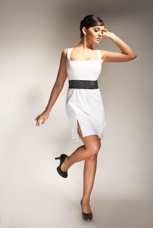 Fashion model Posed on light background in white dress Stock Photo