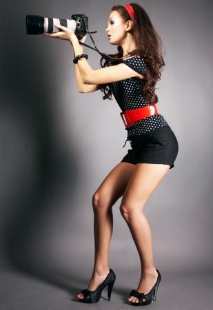 Fashion girl posing with camera on black background