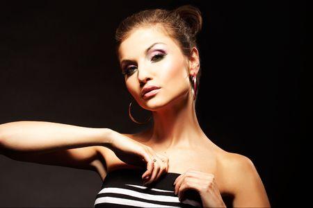 brunette  girl posing in studio on dark background photo