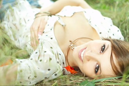 head down: beautiful girl lying down of grass with white dress