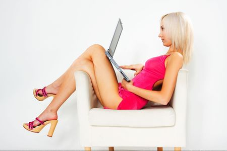girl in pink dress sitting on white chair with laptop photo