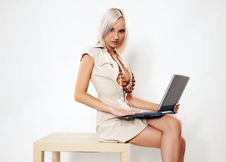 girl in beige costume sitting with laptop