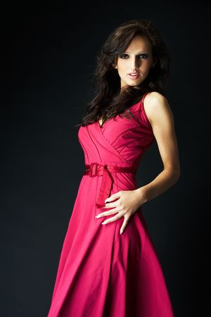 girl wearing a nice ping dress on black background photo