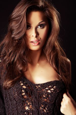 beautiful and y brunette girl on dark background - portrait