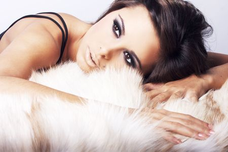 Sexy woman in lingerie lying on fur looking at viewer.