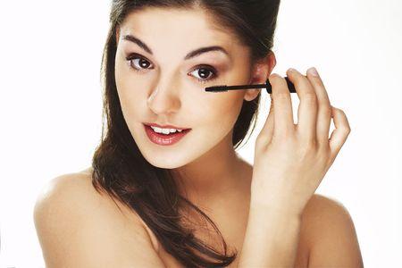 Pretty woman applying make up photo