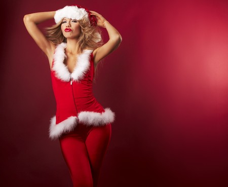 Portrait of beautiful sexy girl wearing santa claus clothes on red background Stock Photo - 3990269