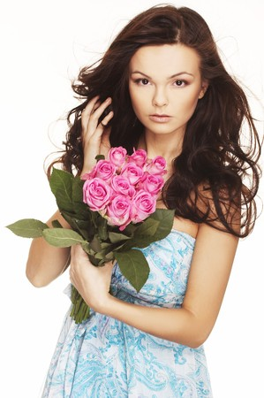 beautiful brunette with pink roses and wind blow hair