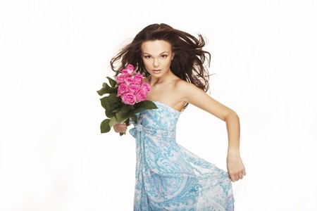 beautiful brunette with pink roses and wind blow hair photo