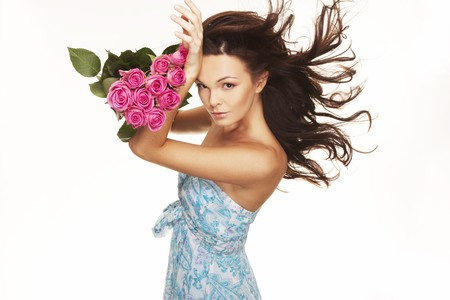windblown: beautiful brunette with pink roses and wind blow hair