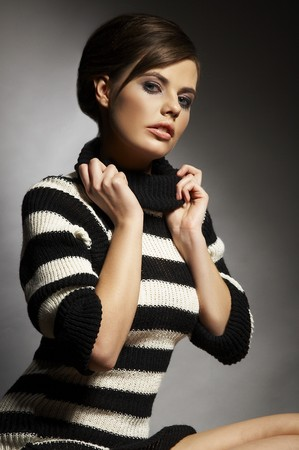 gril: sweet gril in black and white sweater on dark background Stock Photo