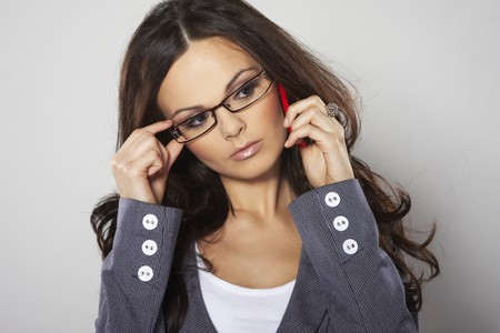 mobilephones: Attractive businesswoman with cell phone and eye glasses  Stock Photo