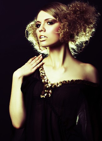 bobbed: fashion model with curly hair in black tunic in black background Stock Photo