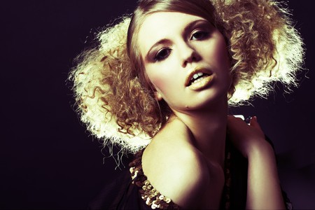 fashion model with curly hair in black tunic in black background Stock Photo