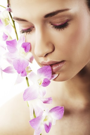 Beautiful young woman with orchid flowers 写真素材