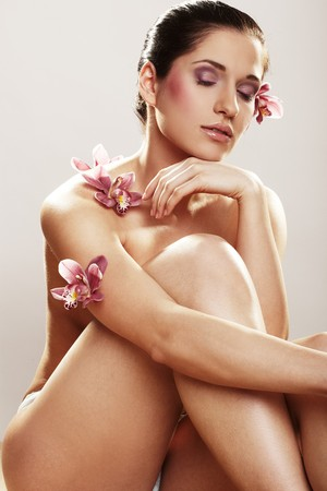 Beautiful young woman with orchid flowers on light background Stock Photo