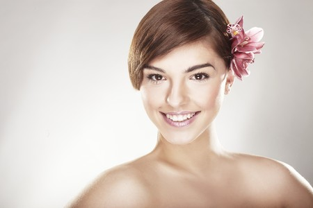 happy young woman with orchid on light background