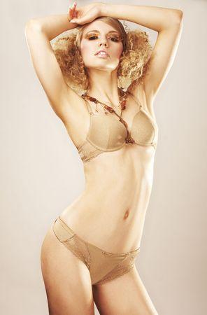 sexy fashion model in gold bikini