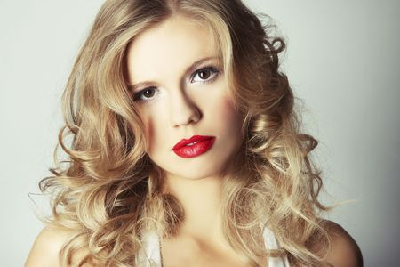 sexy blond girl with red lips on grey background