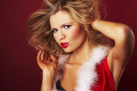 Sexy santa helper on red background photo