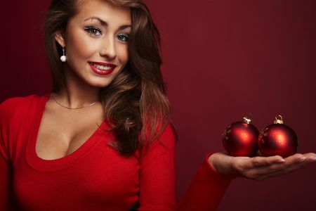 sexy xmas elf: Attractive Woman Holding Red Ornaments on a red Background.