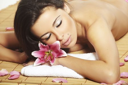 Portrait of Fresh and Beautiful brunette woman laying on bamboo mat photo