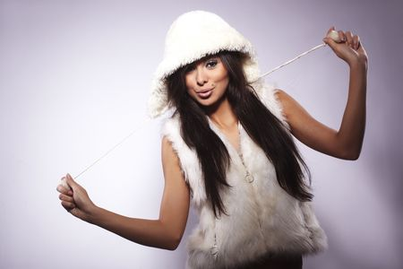 Portrait of teen girl wearing fur lined coat hood and smiling against white background. photo