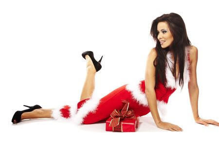 Young woman wearing santa claus and holding red gift on white background
