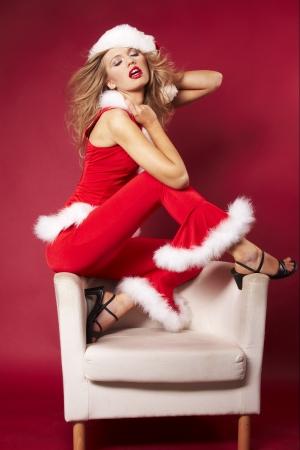 Sexy santa helper on red background photo