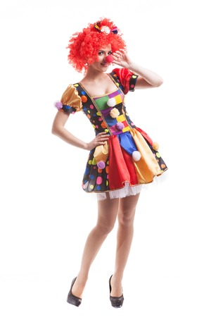 Attractive woman clown with red hair on a white background photo