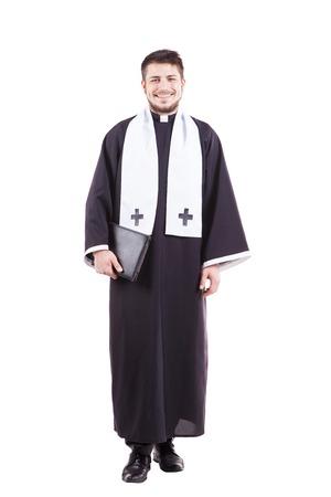 sacerdote: Sacerdote joven que sostiene una biblia santa aislado en el fondo blanco