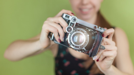 smiling girl with vintage  retro camera taking photo on green background photo