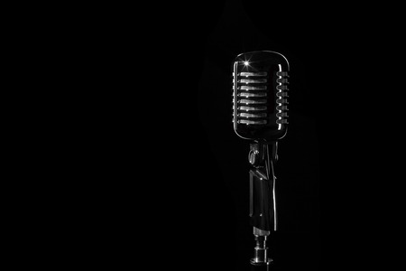 Vintage retro microphone isolated on black background photo