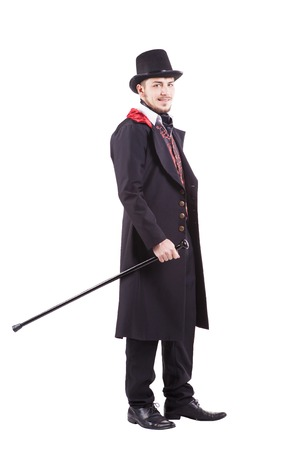 Retro fashion man with beard wearing black suit Holding a walking stick. Isolated in white background