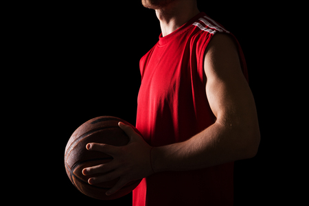 ball sport: Athletic basketball player holding ball isolated on black background Stock Photo