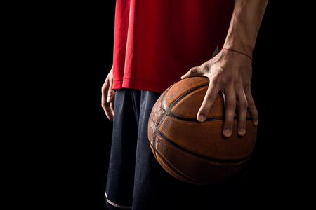 Speler houdt een bal van het basketbal in de hand op de zwarte achtergrond Stockfoto